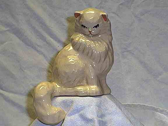 Photo of figurine of white cat with tail hanging over edge